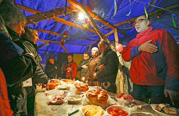 Unas personas cantan el himno nacional antes de una cena durante una celebración de la navidad ortodoxa en Kiev (Ucrania) | Foto: EFE/Sergey Dolzhenko