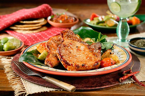 Unas chuletas de cerdo al horno con salsa de tomate es una opción nutritiva y saludable para la cena navideña | Foto: EFE