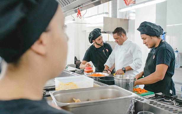 Juan Miguel Cabrera, chef ejecutivo del hotel Bahía del Duque, junto a los jóvenes del proyecto FOCA, durante la elaboración del menú