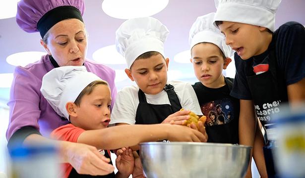 La chef Isabel Alonso y sus jóvenes alumnos, durante la clase de cocina   Foto: A. Gutiérrez