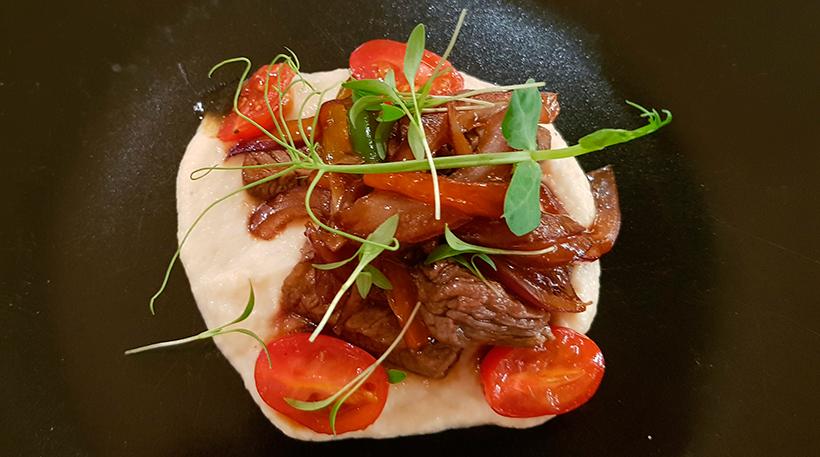 Lomo de ternera salteado con cebollas encurtidas, tomates y puré de apio nabo en el restaurante Alisios Market Food | Foto: J.L.C.
