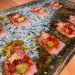 Usuzukuri de toro, con crema de aguacate, tomate liofilizado y crujiente de pan